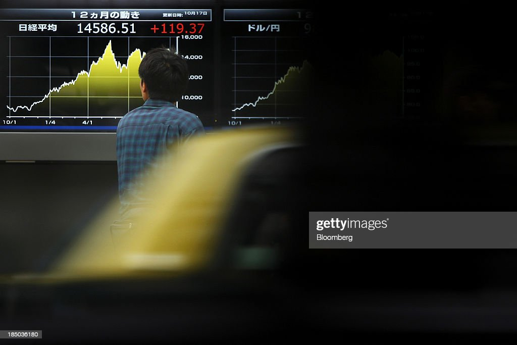 A man is seen through the window of a passing vehicle as he looks at an electronic stock board displaying the closing figure of the Nikkei 225 Stock Average and its movements over the past 12 months in Tokyo, Japan, on Thursday, Oct. 17, 2013. Japanese shares rose, with the Topix index climbing to a three-week high, after the U.S. Congress voted to end the government shutdown and raise the debt ceiling, ending the nation's fiscal impasse. Photographer: Kiyoshi Ota/Bloomberg via Getty Images