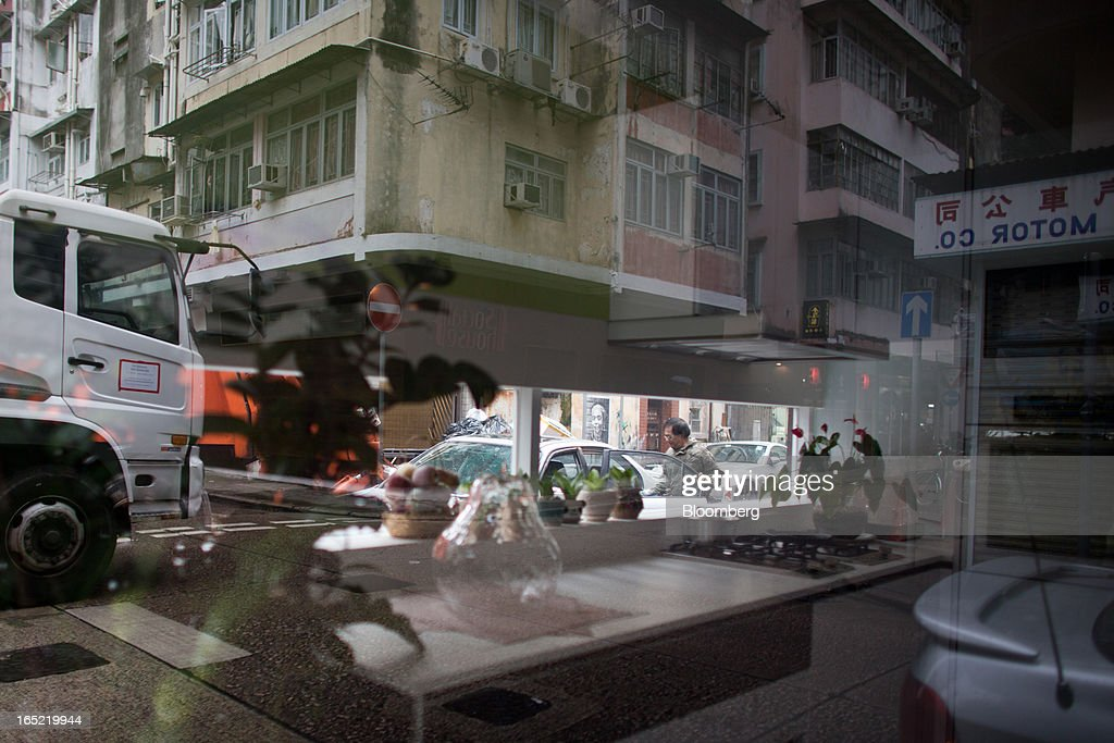 A man is seen through the windows of an interior design store on a street corner in the Tai Hang area of Hong Kong, China, on Saturday, March 30, 2013. Rents are climbing in neighborhoods near Causeway Bay and Hong Kong's other prime shopping districts, known for luxury stores that attract free-spending tourists from mainland China. That's squeezing out mom-and-pop shops, congee and noodle vendors as developers and landlords seek to profit from the trend. Photographer: Lam Yik Fei/Bloomberg via Getty Images