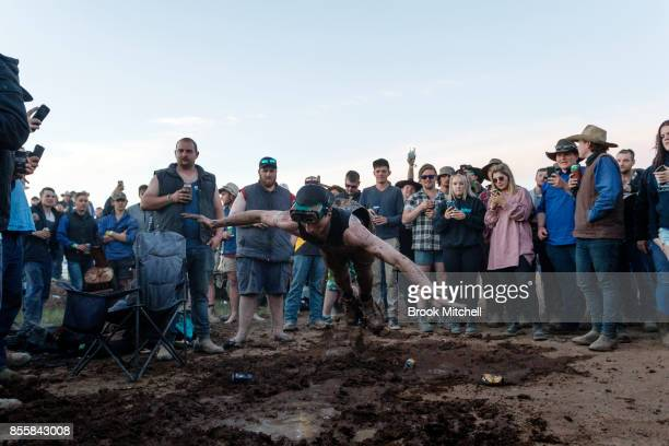 A man is seen throwing himself into a makeshift mud pit on the wild final evening of the 2017 Deni Ute Muster on September 30 2017 in Deniliquin...