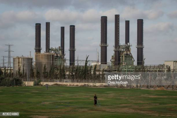 A man is seen watering a football field in front of Gaza's only power plant in the Nusseirat district on July 19 2017 in Gaza City Gaza For the past...