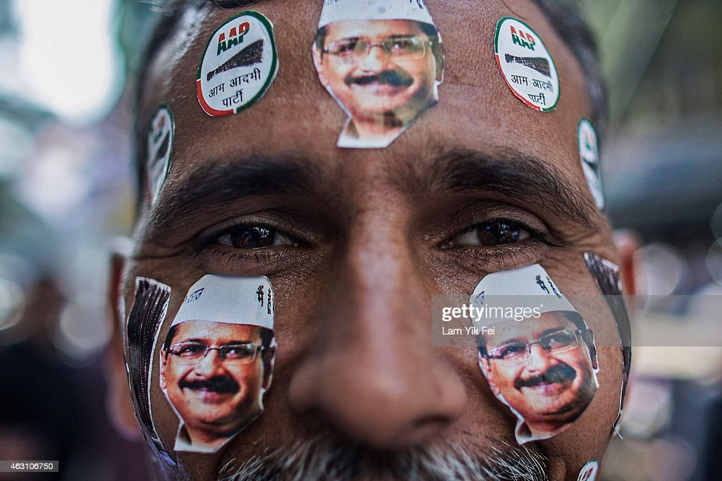 A man is seen with Aam Aadmi Party (AAP) leader Arvind Kejriwal stickers on his face as he watches the results of Delhi Assembly Elections at the party Patel Nagar Office on February 10, 2015 in Delhi, India. Arvind Kejriwal and his AAP party have taken victory in Delhi's state elections which will see Kejriwal return for a second time as Delhi's chief minister.