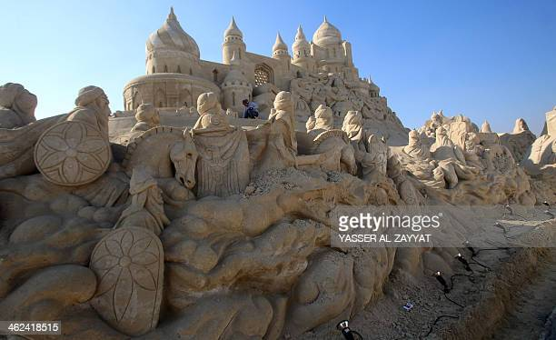 A man is seen working on a sand sculpture at Kuwait's sand village at Mishref Fairground in Kuwait City on January 13 2014 Sculptors from Kuwait and...
