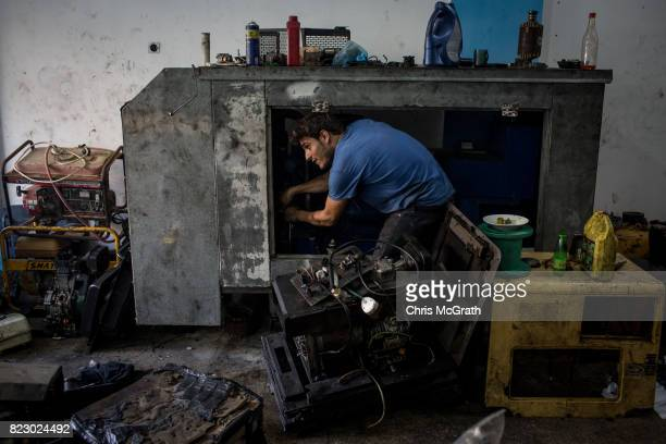 A man is seen working to fix a generator at a repair shop on July 19 2017 in Gaza City Gaza For the past ten years Gaza residents have lived with...
