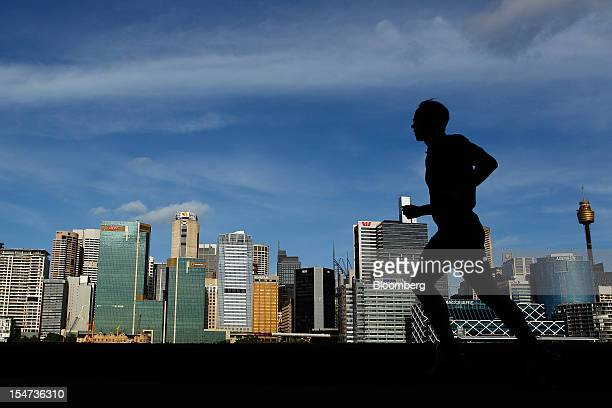 A man is silhouetted as he jogs past a view of the central business district in Sydney Australia on Tuesday Oct 23 2012 Treasurer Wayne Swan on...