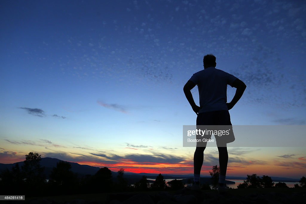 A man is silhouetted as he takes in the sunset over Moosehead Lake in Greenville, ME on August 25, 2014.