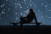 A man is sitting on a bench and using a smartphone. Forest and starry sky bokeh In the background