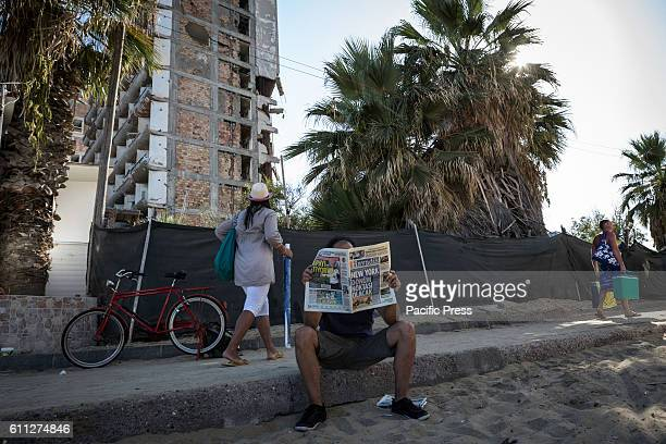 A man is sitting on a pavement and reading a newspaper Cover is about the peace talks held in New York On the background there is fenced of Varosha...
