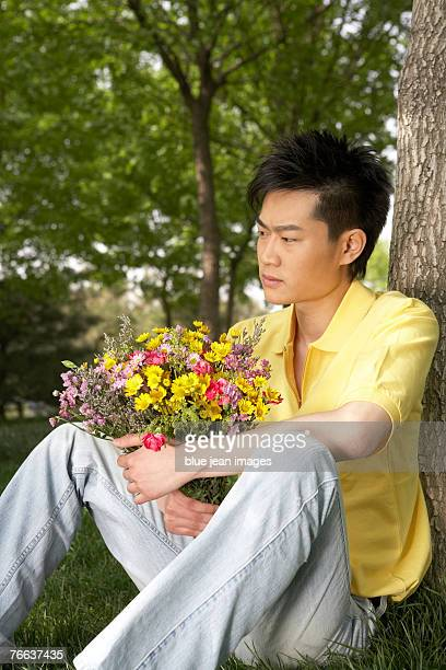 A man is sitting under the tree with a bouquet.
