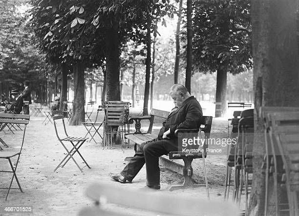 A man is sleeping on a bench in the Jardin des Tuileries in May 1929 in Paris France