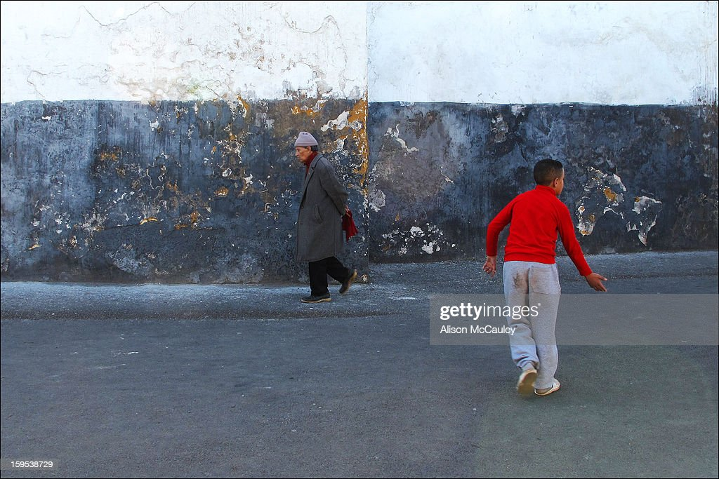 CONTENT] A man is slowly walking in front of an old, characterful wall. Further along a boy runs in a different direction. The boys red sweater stands out against the otherwise gray, white and black scene.