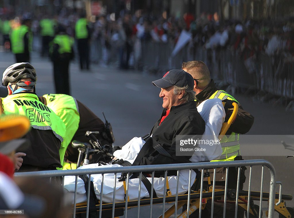 A man is smiles as he is wheeled on a stretcher from the route on Copley Square The Boston Red Sox celebrate their World Series victory with a...