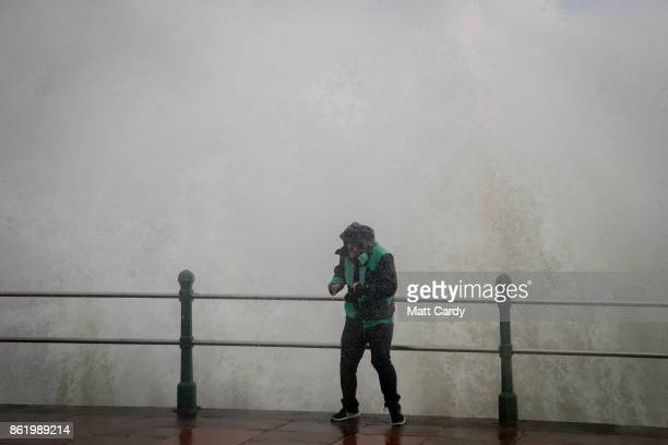 A man is soaked by a wave whipped up by Hurricane Ophelia crash over the seafront in Penzance on October 16 2017 in Cornwall England Hurricane...