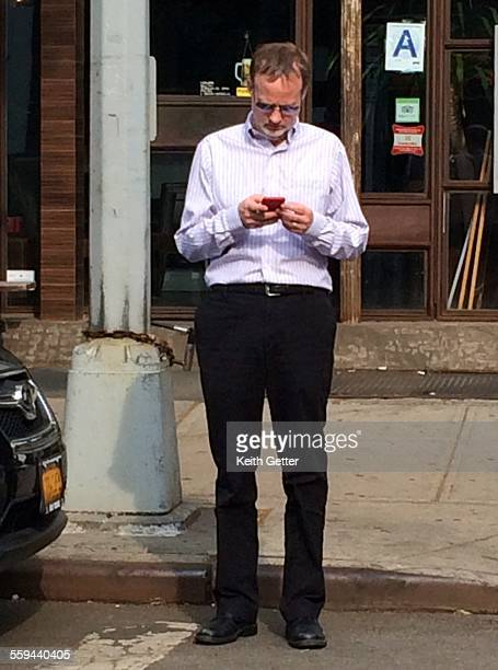 A man is standing in the street just past the curb looking down at his cell phone in the Boerum Hill neighborhood of Brooklyn NYC May 28 2015