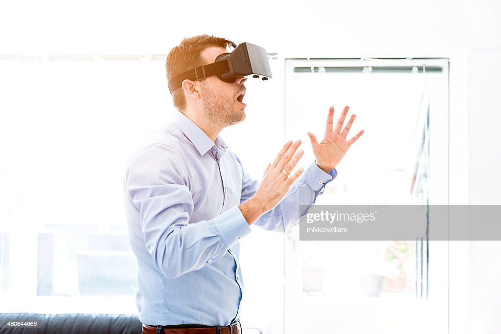 Man is surprised while using a virtual reality headet