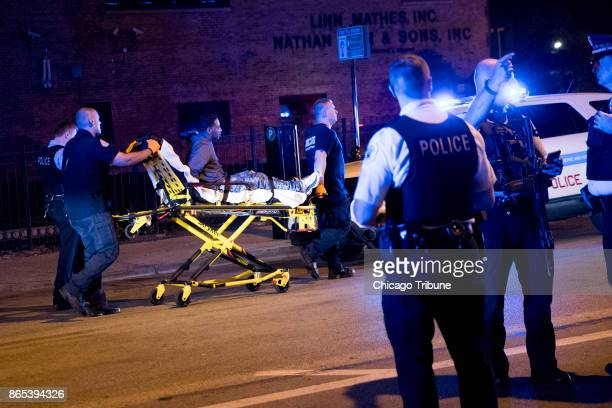 A man is taken away on a stretcher at the scene where three people were shot on Saturday Oct 21 2017 at a Taco Burrito King Restaurant in Chicago Ill