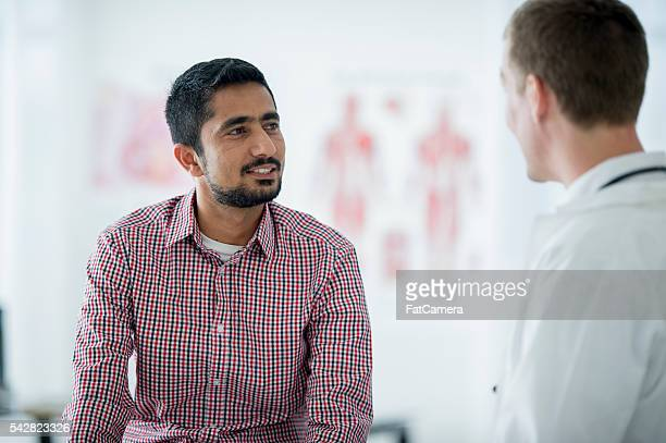 A man is talking with his doctor at an appointment.