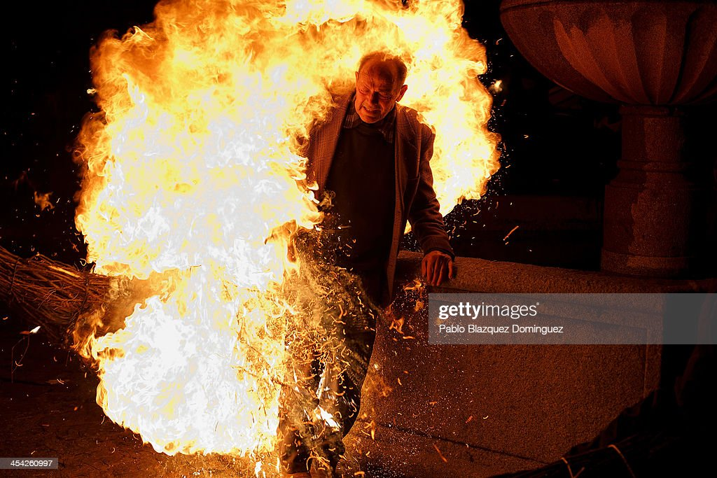 A man is touched by the flames of a burning broom during 'Los Escobazos' Festival on December 7, 2013 in Jarandilla de la Vera, Spain. Although the origin of 'Los Escobazos' is unknown, it is believed that goat shepherds used to walk down from Gredos mountains to the village to cerebrate the Immaculate Conception procession lighting their way with broom torches. The ritual takes place every December 7, one day before Immaculate Conception day, because the following morning shepherds had to be back with their herd in the mountains. Villagers also used to bring their donkeys to the procession on the belief that this would bless them keeping illnesses away from them. At nightfall people make bonfires in the streets and start a battle with burning brooms, followed by the Immaculate Conception Procession.