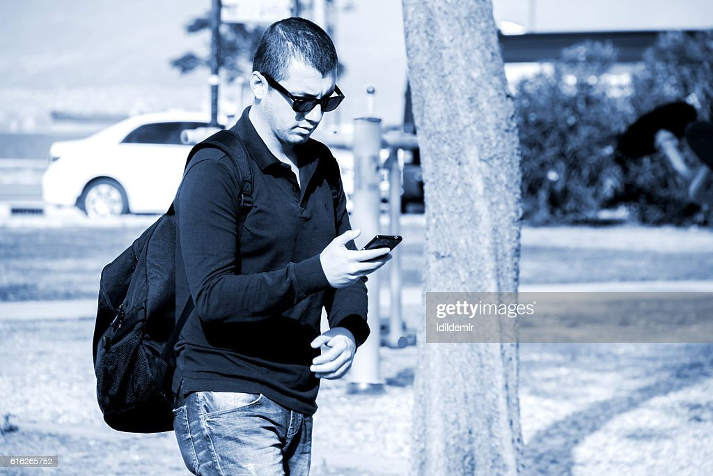 Man Is Walking And Looking To His Smartphone : Stock Photo
