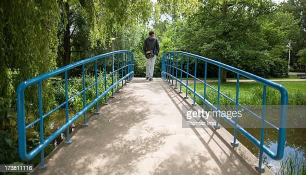 A man is walking over a bridge in the Vondelpark on June 25 2013 in Amsterdam Netherland