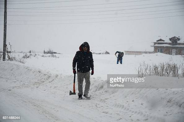 A man is walking with an ax as snow falls at the streets of Svilengrad Bulgaria on January 11 2017 Snow paralyse Bulgaria The snow reached 40 70 sm...
