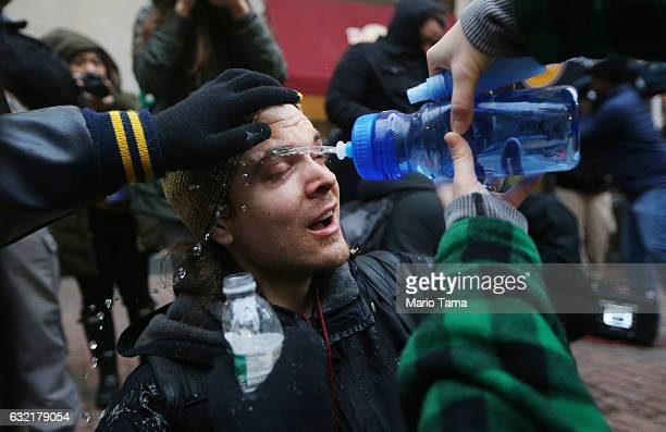A man is washed with water after being sprayed by police pepper spray during an antiTrump demonstration on January 20 2017 in Washington DC...