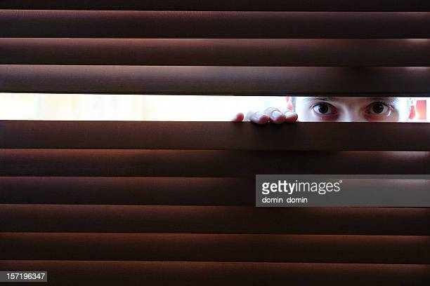 Man is watching through hole in window's wooden blinds
