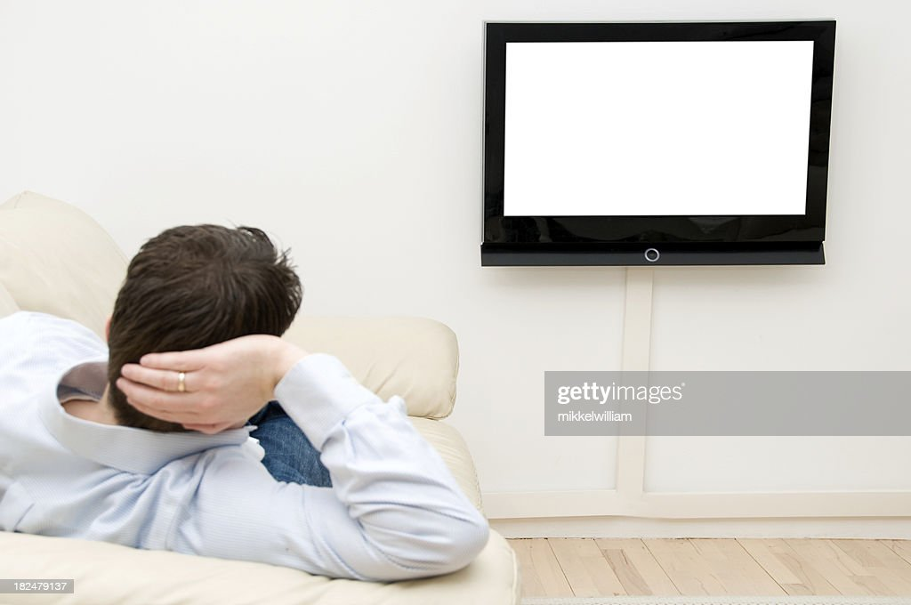 watching tv at home. man is watching tv from a sofa at home : stock photo
