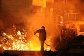 Man is working in the splashing molten iron
