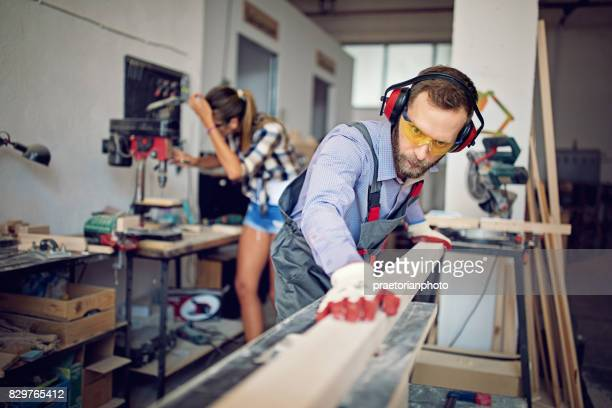 Man is working with machinery and timber in a small family carpenter factory