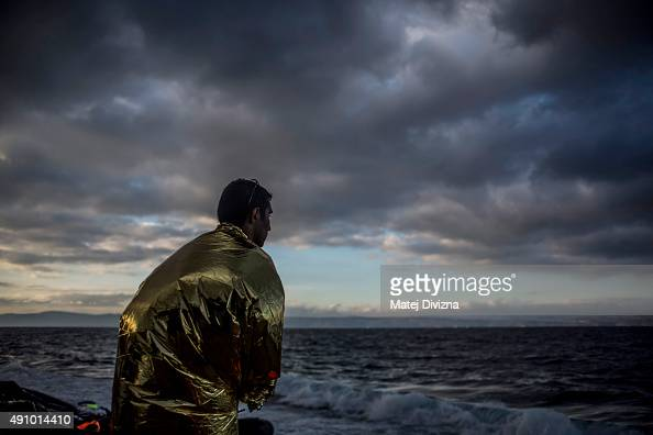 A man is wrapped with thermal blanket to shelter from cold as he arrived with other refugees on the shores of the Greek island of Lesbos after...