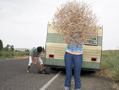 man jacking up trailer, woman holding tumbleweed