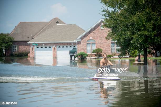 A man jetskis down a flooded residential neighborhood in Port Arthur Texas September 1 2017 Stormweary residents of Houston and other Texas cities...