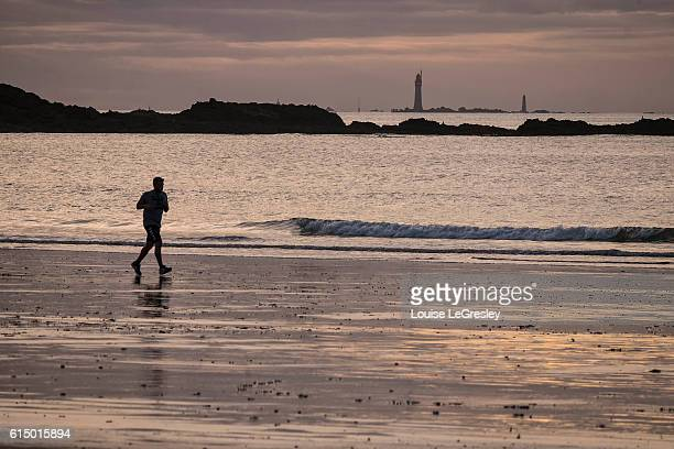 Man jogging along the beach at sunset in Saint-Malo, France