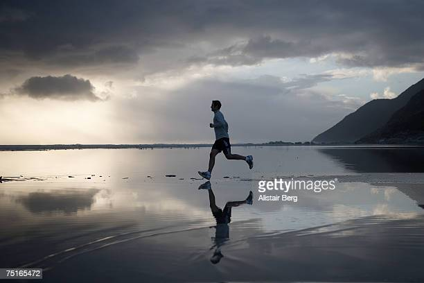 Man jogging in shallow water on beach at dusk, side view