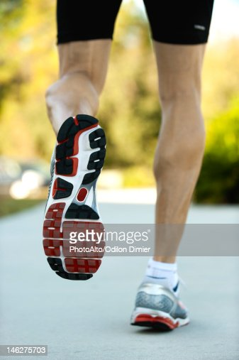 Man jogging, low section, rear view