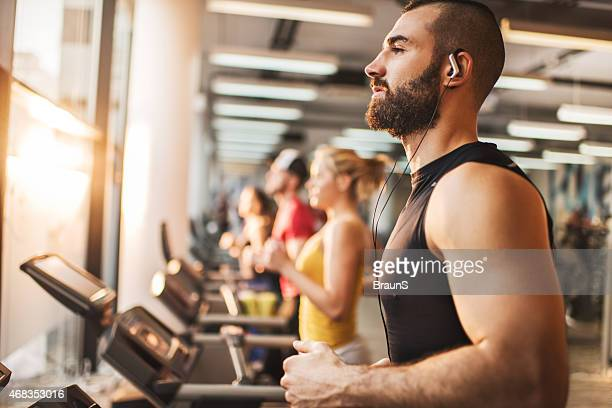 Man jogging on a treadmill in a health club.