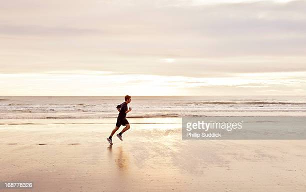man jogging on beach at sunrise
