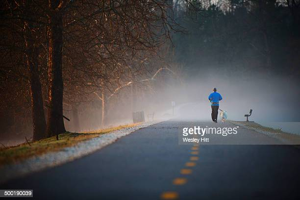Man jogging on morning trail with dog