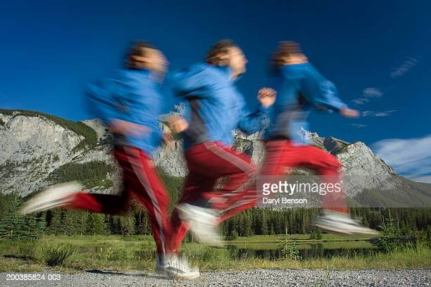 Man jogging on path (blurred motion) (multiple exposure)
