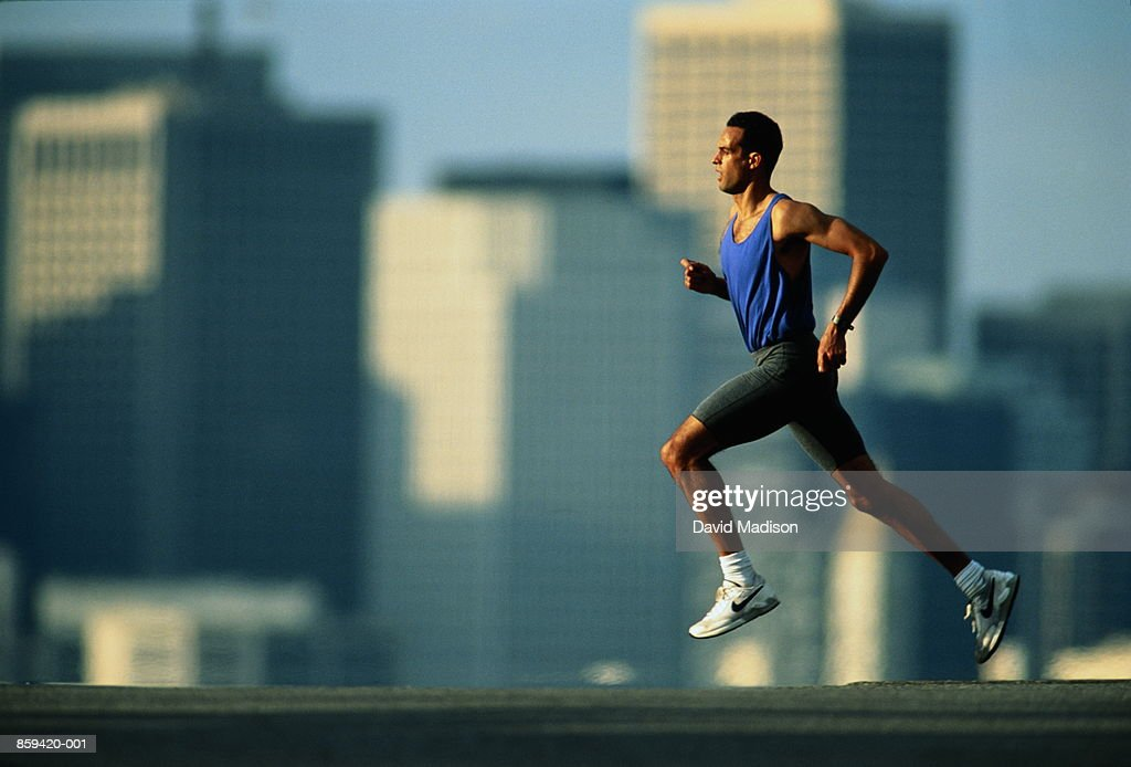 Man jogging on urban street, buildings in background : Stock Photo