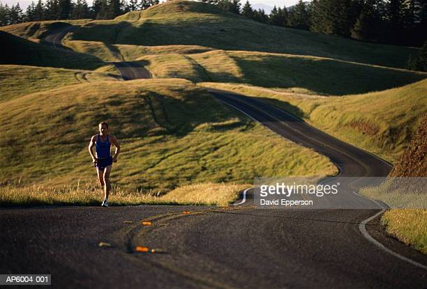 Man jogging on winding country road