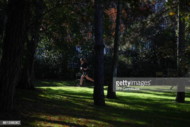 A man jogs at the Jardin du Luxembourg in Paris on October 15 2017 during unusually warm autumnal temperatures / AFP PHOTO / CHRISTOPHE ARCHAMBAULT
