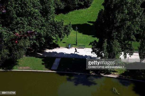 A man jogs at the Parc des Buttes Chaumont in Paris on June 9 2017 / AFP PHOTO / CHRISTOPHE ARCHAMBAULT