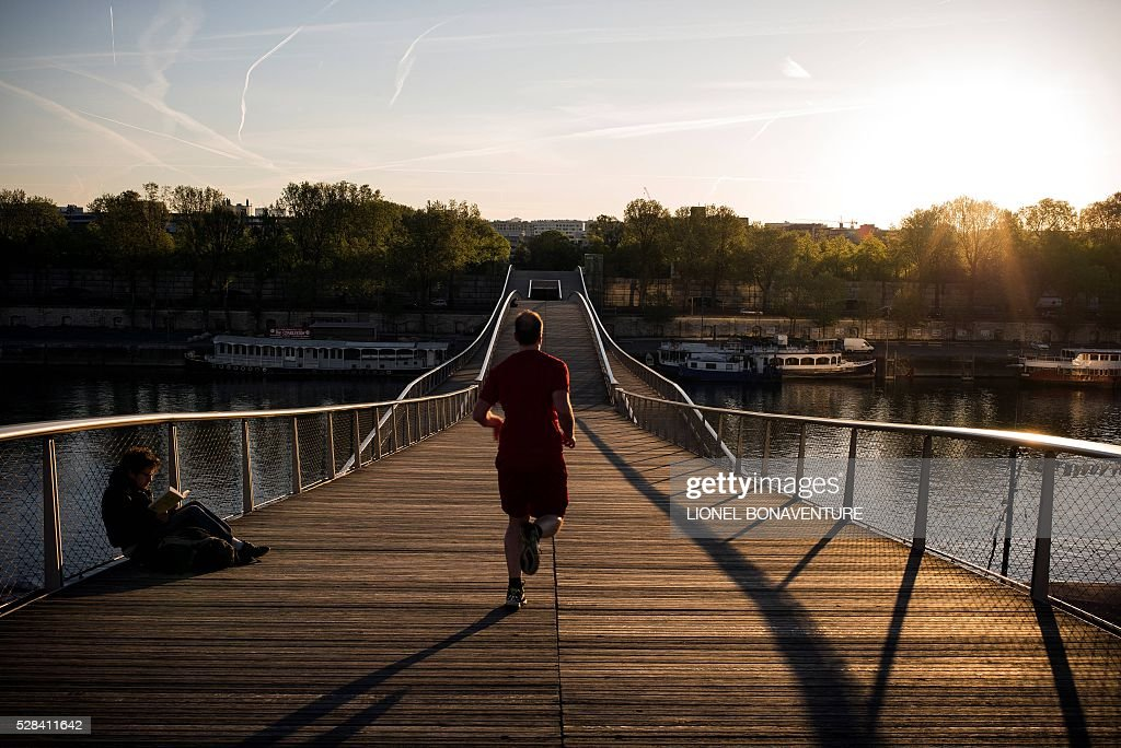A man jogs by a man reading a book on a bridge above the Seine river, on May 5, 2016 in Paris. / AFP / LIONEL