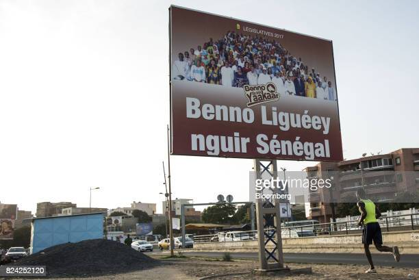 A man jogs by an electoral sign in Dakar Senegal on Friday July 28 2017 Senegalese voters will elect a new parliament on Sunday in a vote that was...