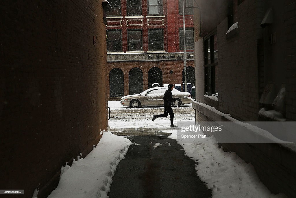 A man jogs down a street during heavy snow on February 5, 2014 in Burlington, Vermont. Burlington, and much of the Northeast, received another mix of wintery weather on Wednesday causing traffic accidents and hundreds of flight cancelations.
