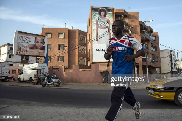 A man jogs in front of an advertisement for Mango fashion in Dakar Senegal on Friday July 28 2017 Senegalese voters will elect a new parliament on...