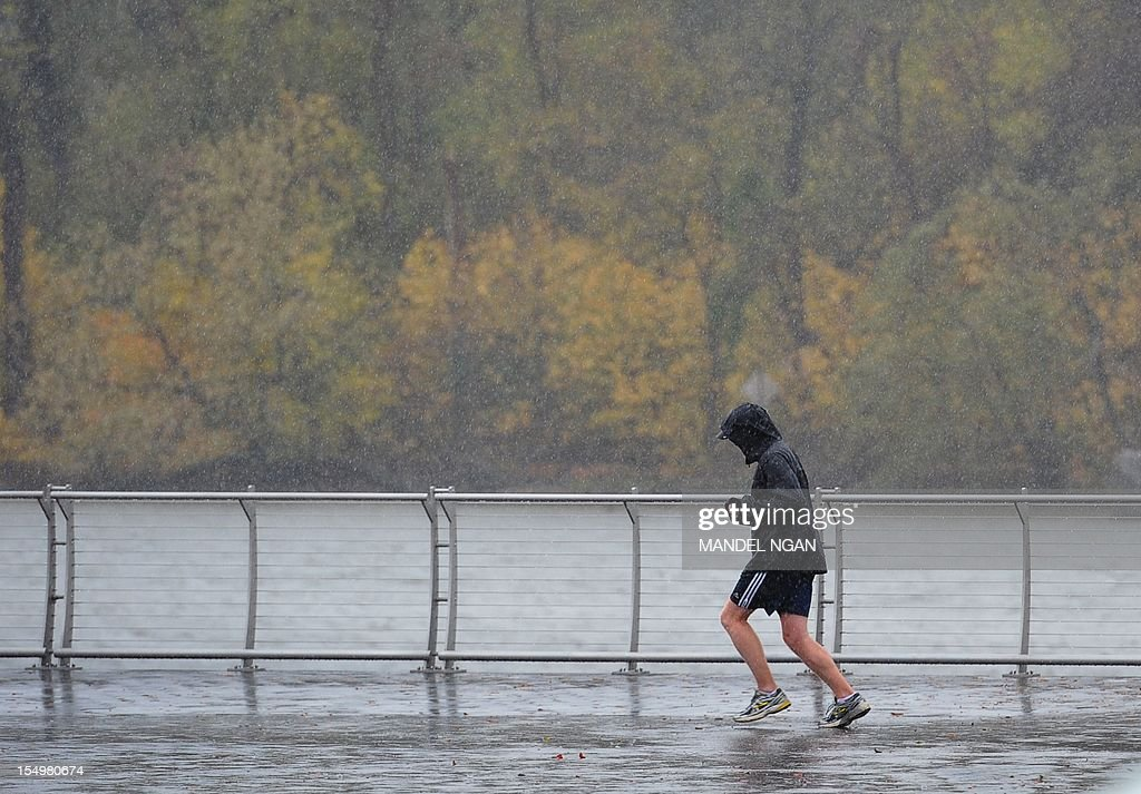 A man jogs in the Georgetown Waterfront park along the Potomac River in the historic Georgetown neighbourhood of Washington on October 29, 2012 as Hurricane Sandy approaches. Sandy intensified as it roared toward the US East Coast, bringing New York, Washington and other major cities to a virtual standstill, amid warnings of life-threatening floods. AFP PHOTO/Mandel NGAN