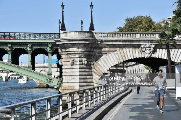 A man jogs on a road which was turned into a pedestrian area on the bank of the Seine River in Paris on September 14 2016 on the opening day of the...