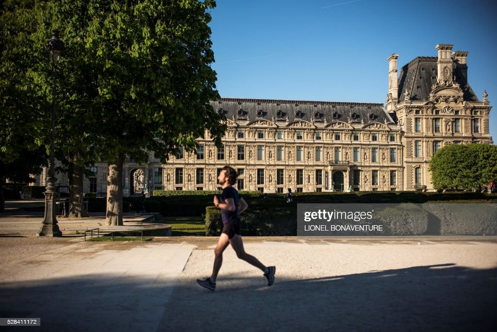 A man jogs on a sunny day at the Tuileries garden on May 5, 2016 in Paris. / AFP / LIONEL